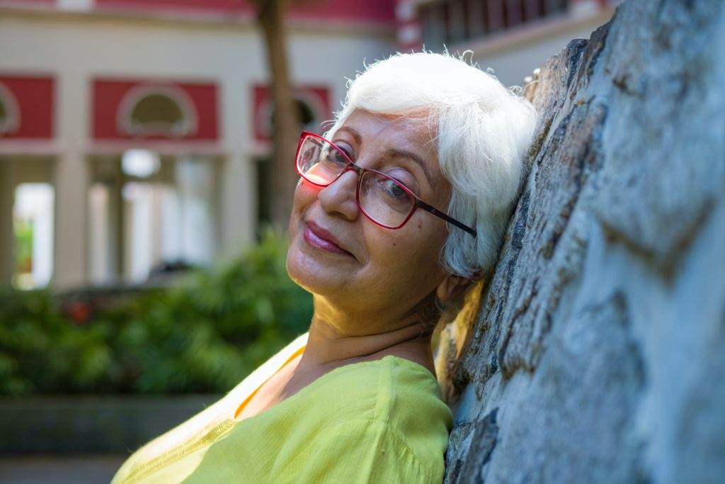 Smiling woman wearing glasses leaning against a tree